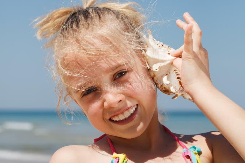 Menina que tem o divertimento em uma praia fotografia de stock