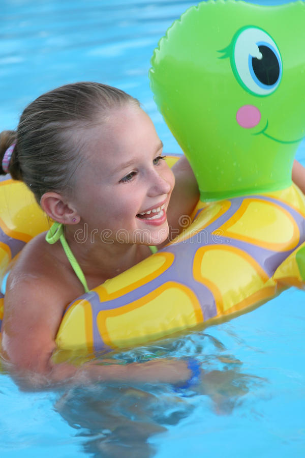 Menina que tem o divertimento na água azul foto de stock royalty free