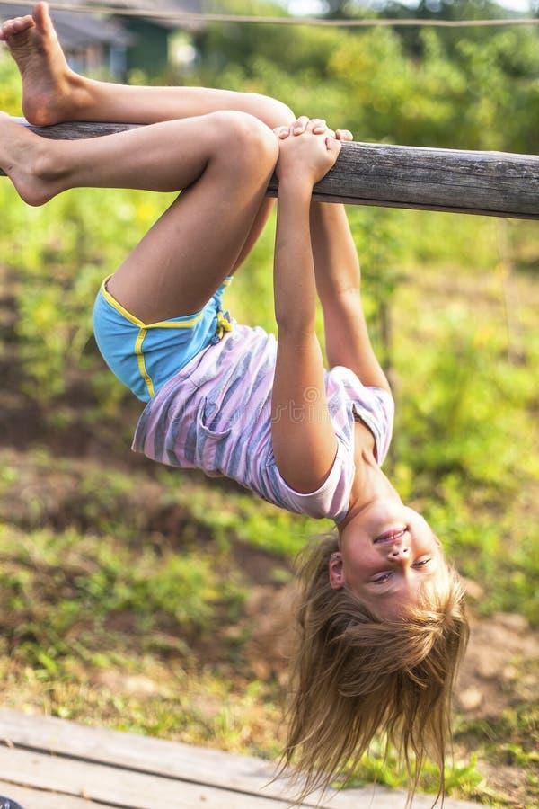 Menina que tem o divertimento na suspensão do parque de cabeça para baixo no campo rural verde imagens de stock royalty free