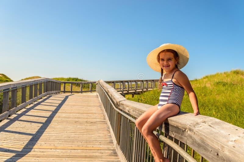 Menina que tem o divertimento no passeio à beira mar à praia de Brackley imagens de stock