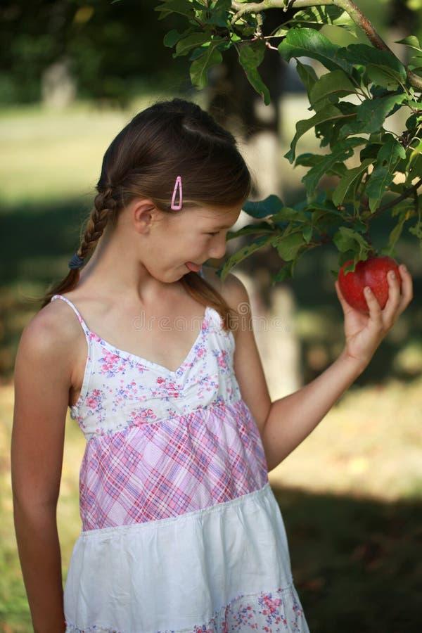 Menina que tem um apetite para uma maçã imagem de stock royalty free