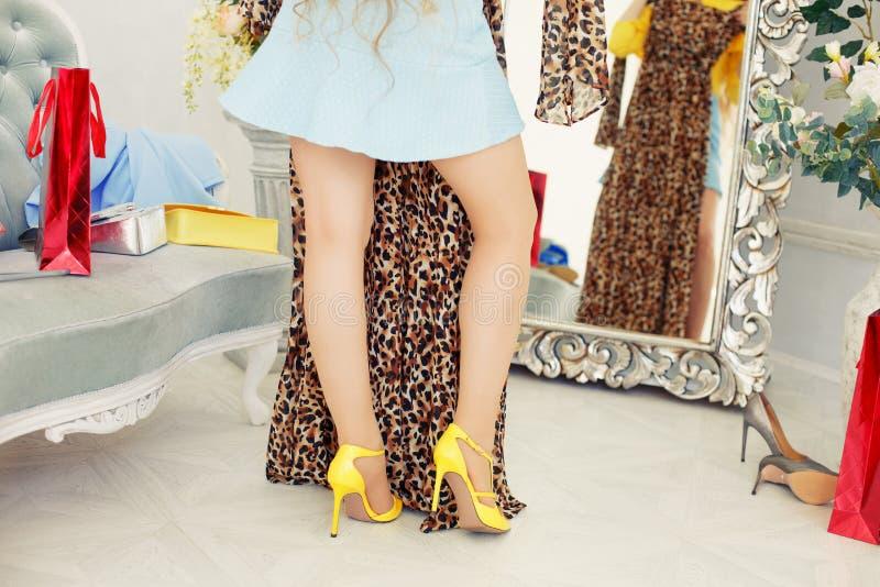 Menina que tenta em um vestido na frente de um espelho A mulher olha o purc foto de stock royalty free