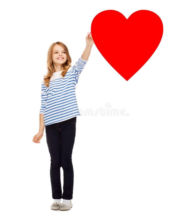 Menina que tira o coração vermelho grande no ar fotografia de stock royalty free