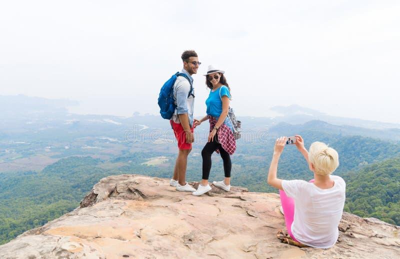 Menina que toma a foto dos pares com as trouxas que levantam sobre a paisagem da montanha no telefone esperto da pilha, homem nov fotos de stock royalty free