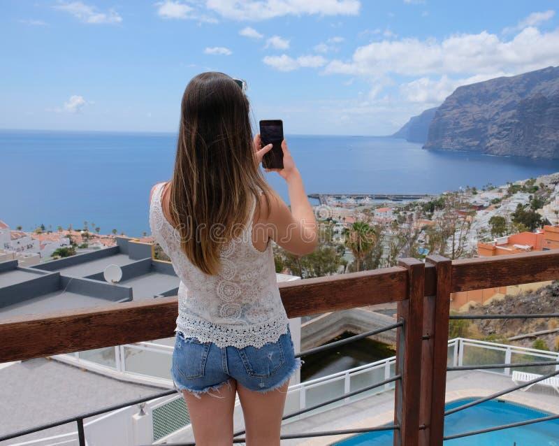 Menina que toma fotos de Los Gigantes da ilha de Tenerife imagens de stock