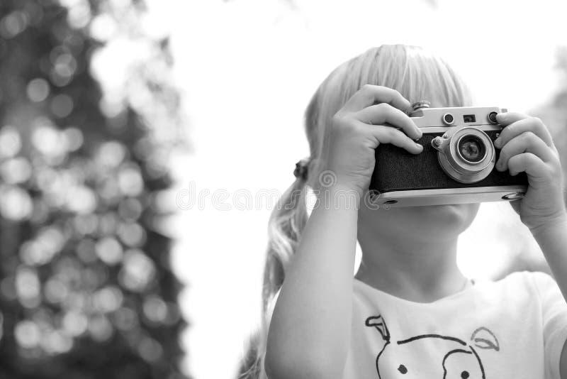 Menina que toma a imagem usando a câmera do filme do vintage fotos de stock royalty free