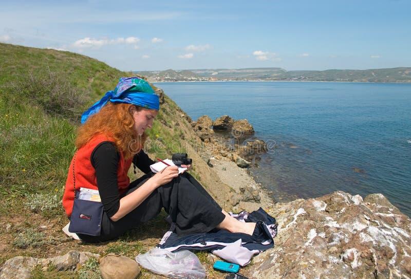 Menina que toma notas na praia imagem de stock royalty free