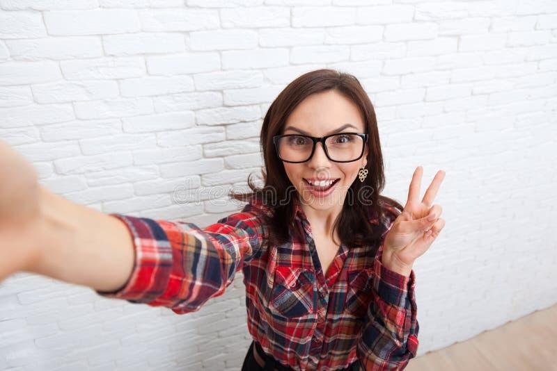 Menina que toma a Selfie a câmera esperta da foto do telefone fotografia de stock royalty free