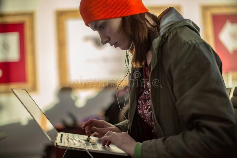 Menina que trabalha com o portátil no salão de espera do aeroporto foto de stock