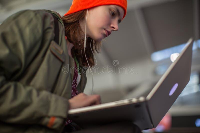 Menina que trabalha com o portátil no salão de espera do aeroporto fotos de stock royalty free