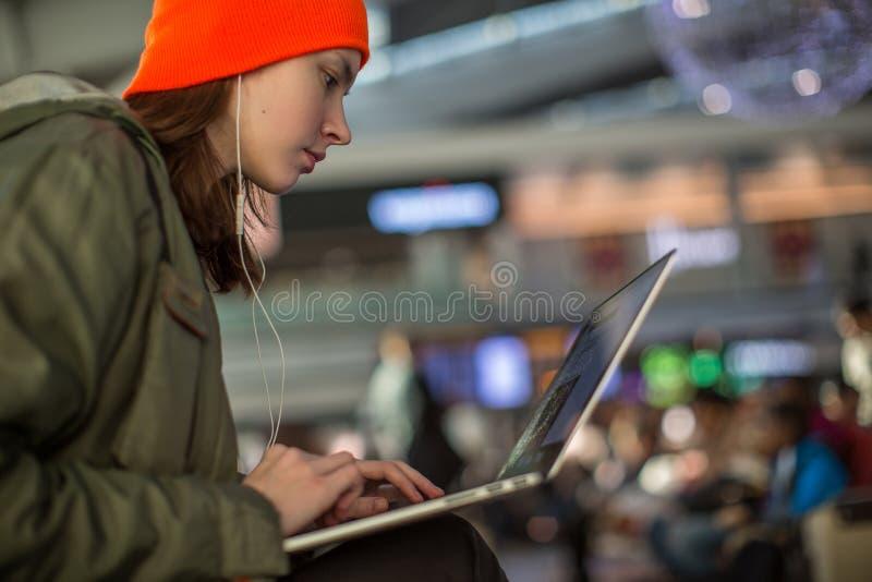 Menina que trabalha com o portátil no salão de espera do aeroporto fotografia de stock royalty free