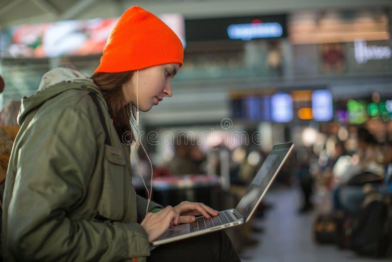 Menina que trabalha com o portátil no salão de espera do aeroporto imagem de stock