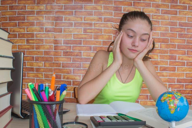Menina que trabalha em seus trabalhos de casa estudante atrativo novo Girl que estuda lições fotos de stock royalty free