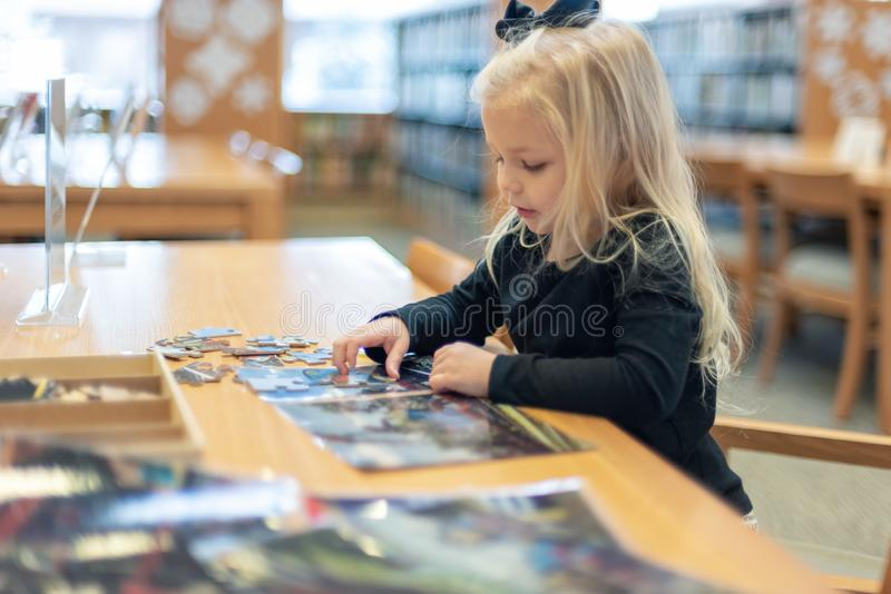 Menina que trabalha na biblioteca do enigma em público fotografia de stock