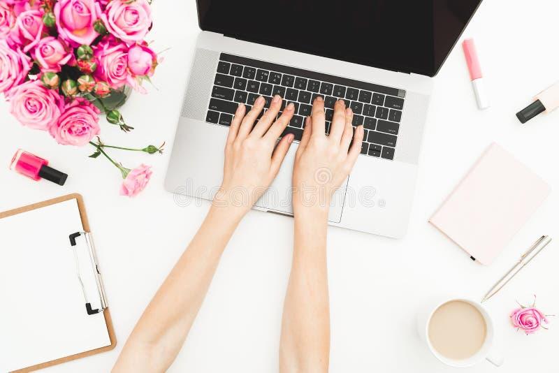 Menina que trabalha no portátil Espaço de trabalho com mãos fêmeas, portátil da mulher, ramalhete cor-de-rosa das rosas, acessóri imagem de stock royalty free