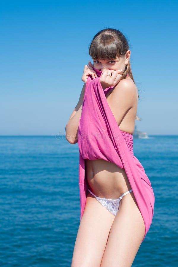 Menina que undressing no mar foto de stock