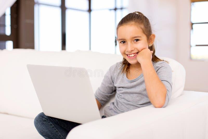 Menina que usa o portátil foto de stock