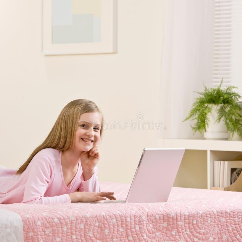 Menina que usa o portátil para o Internet em seu quarto imagem de stock royalty free