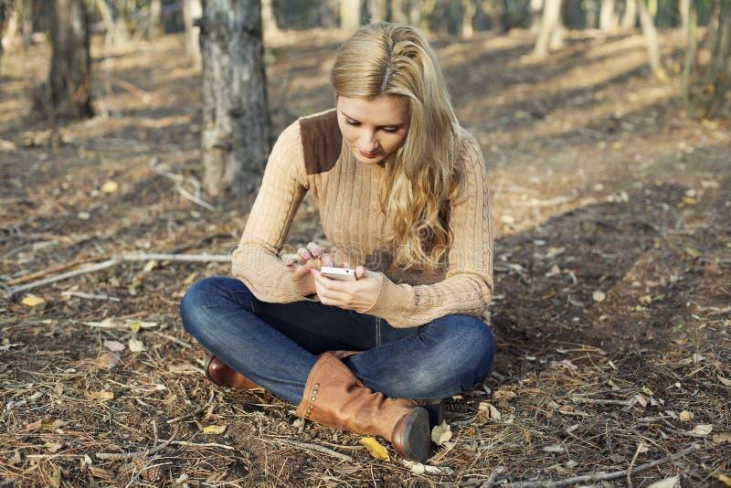 Menina que usa o rádio do Internet no smartphone no natu foto de stock royalty free