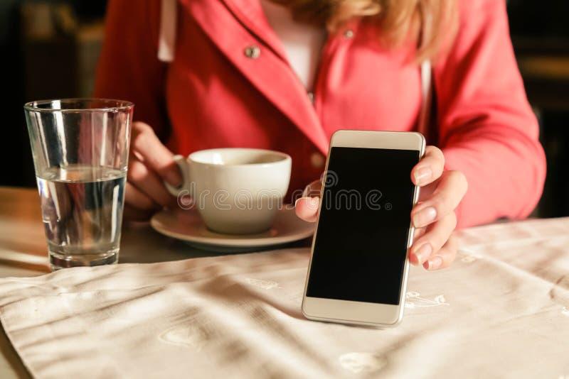 Menina que usa o smartphone e o café da bebida no café Mão que guarda a tela vazia do whit do smartphone foto de stock