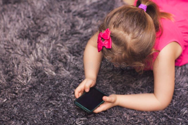 Menina que usa o smartphone em casa imagem de stock