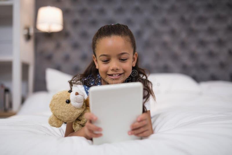Menina que usa a tabuleta digital ao encontrar-se na cama em casa imagem de stock royalty free
