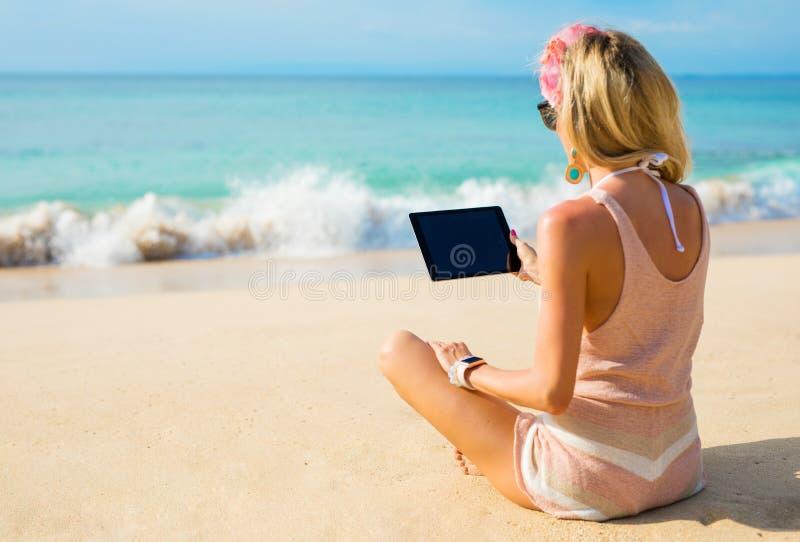Menina que usa a tabuleta na praia foto de stock