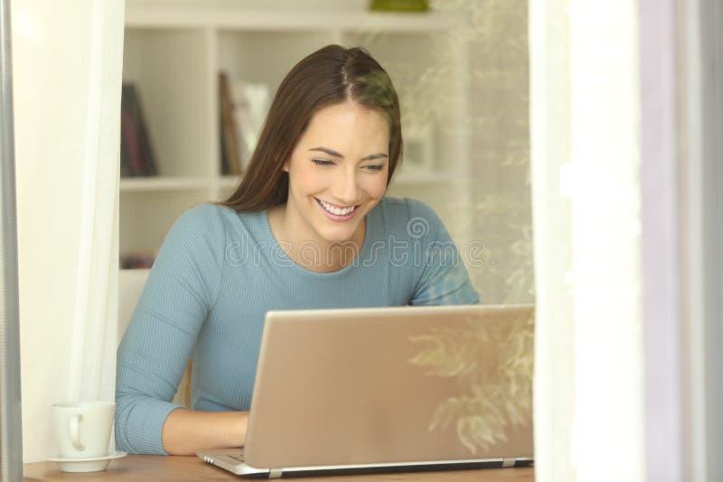 Menina que usa um portátil perto de uma janela em casa imagem de stock royalty free