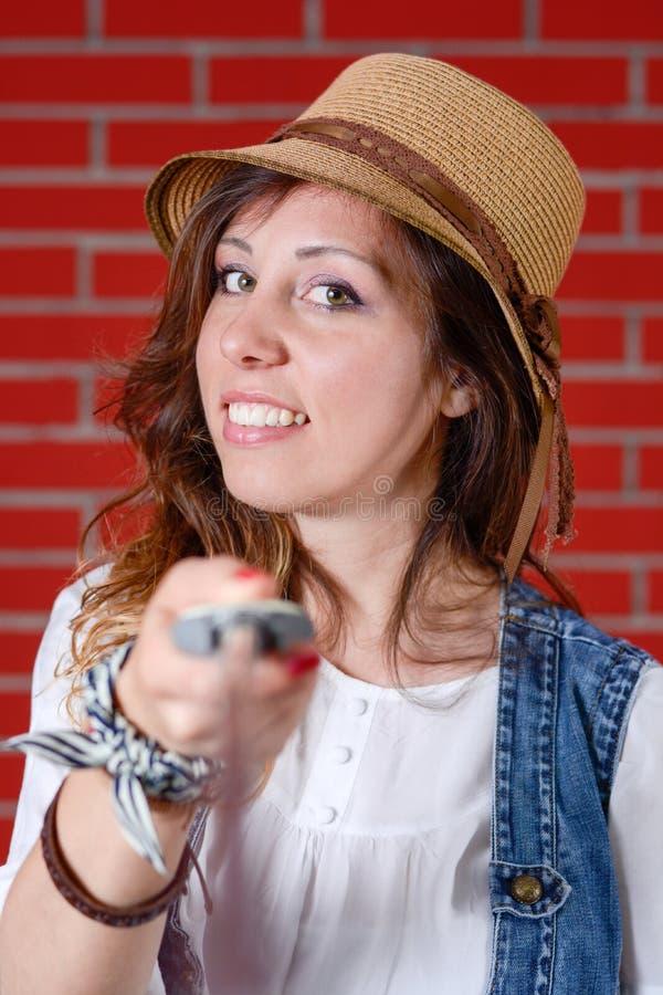Menina que usa a vara do selfie na frente da parede de tijolo imagens de stock