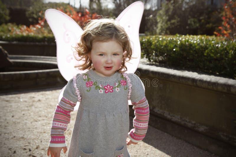 Menina que veste as asas cor-de-rosa da borboleta foto de stock royalty free