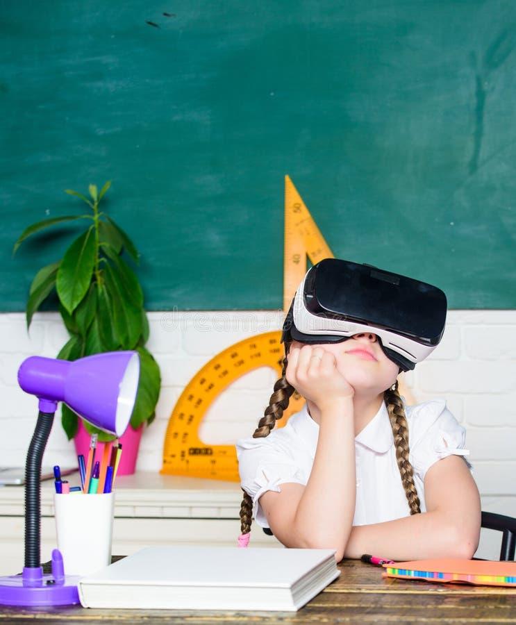Menina que veste ?culos de prote??o da realidade virtual De volta ? escola Crian?a pequena em auriculares de VR a criança veste v imagens de stock royalty free