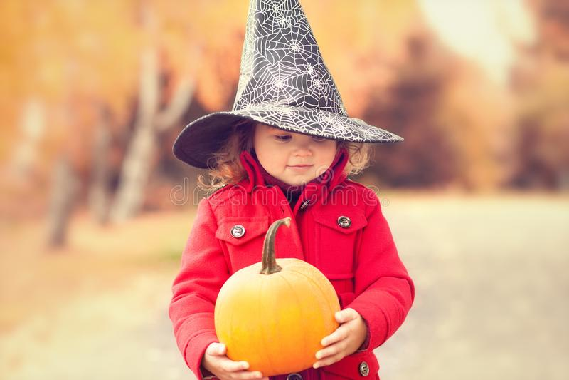 A menina que veste o chapéu da bruxa de Dia das Bruxas e aquece o revestimento vermelho, tendo o divertimento no dia do outono imagem de stock