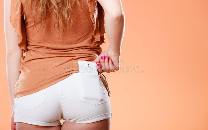 A menina que veste o short toma o telefone do bolso foto de stock