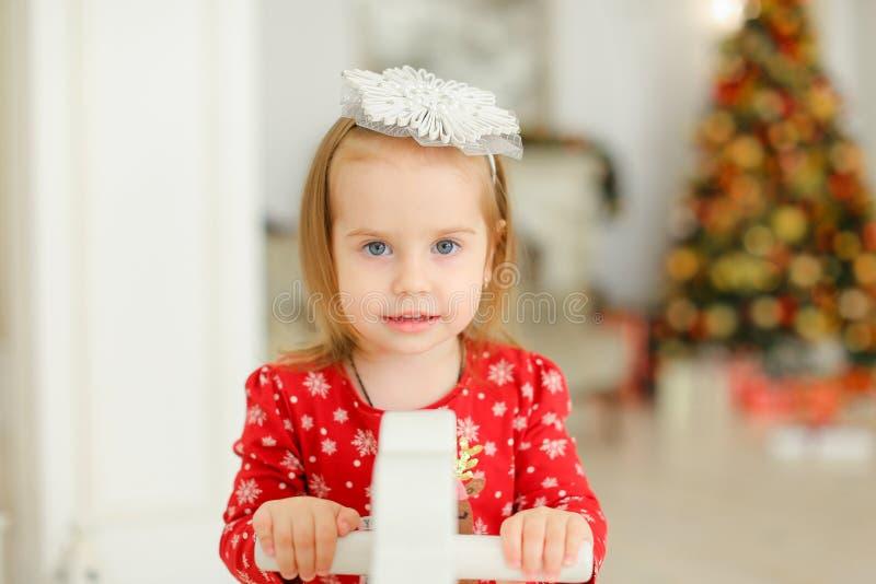 Menina que veste o vestido vermelho que joga com cavalo de balanço, árvore de Natal no fundo borrado imagem de stock