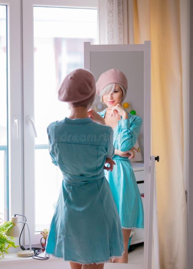 Menina que veste-se acima perto de um espelho foto de stock