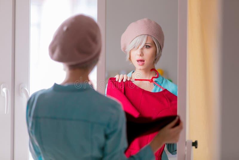 Menina que veste-se acima perto de um espelho fotografia de stock