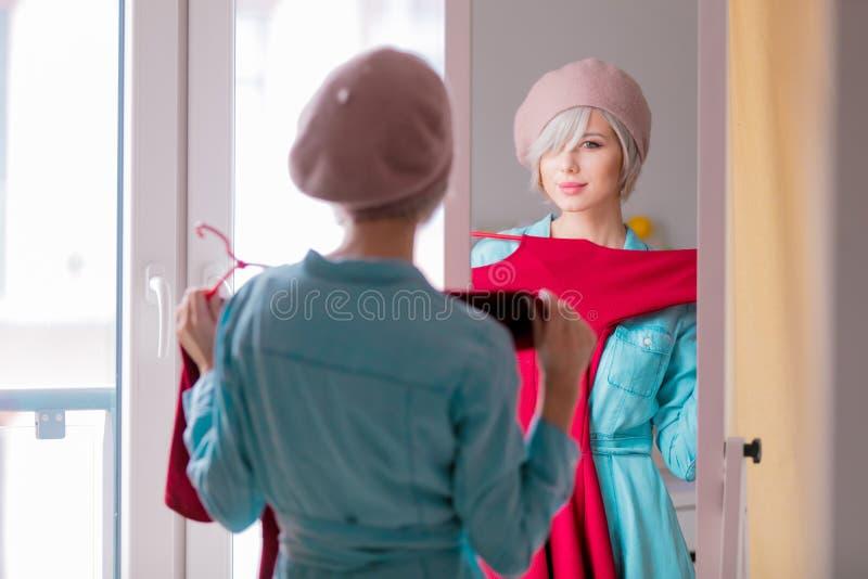 Menina que veste-se acima perto de um espelho imagem de stock