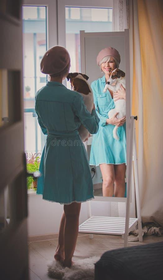 Menina que veste-se acima perto do espelho com cão foto de stock