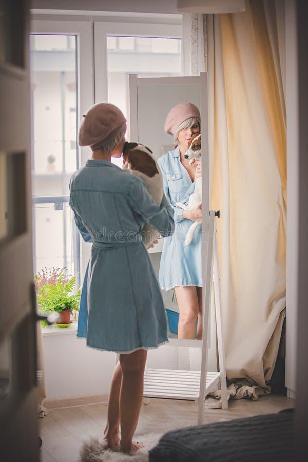 Menina que veste-se acima perto do espelho com cão fotos de stock