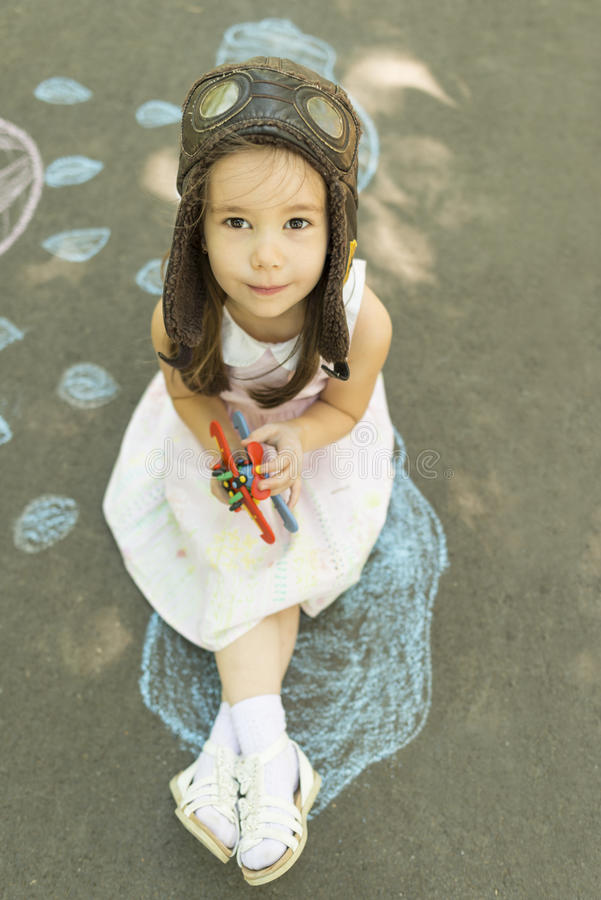 Menina que veste um chapéu piloto com os óculos de proteção que guardam o brinquedo disponivel do biplano fotos de stock