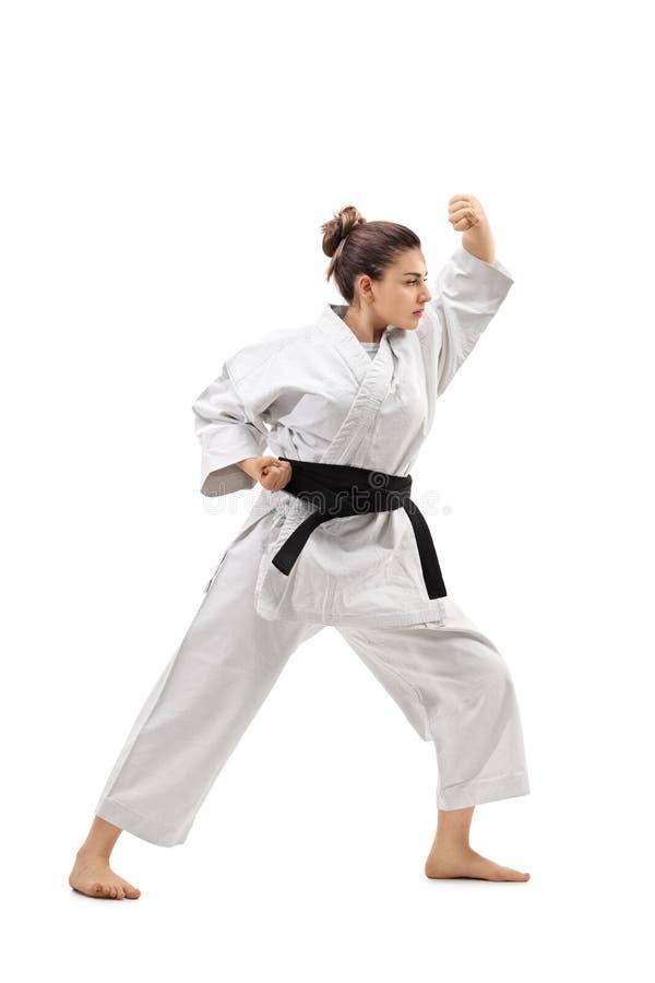 Menina que veste um karaté praticando do quimono foto de stock royalty free