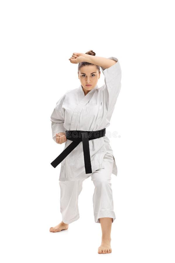 Menina que veste um quimono que faz um kata do karaté fotos de stock royalty free