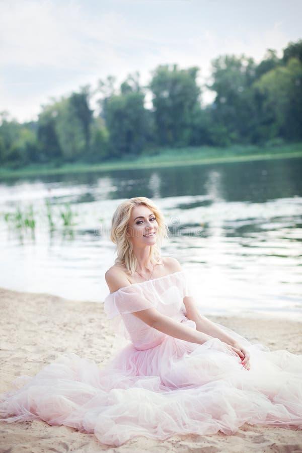Menina que veste um vestido boêmio longo que senta-se na praia em um fim de semana das férias Uma senhora só senta-se na praia ap imagem de stock royalty free