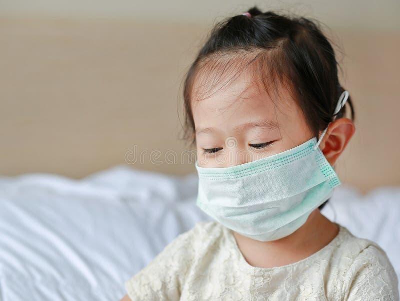 Menina que veste uma máscara protetora que encontra-se na cama imagens de stock royalty free
