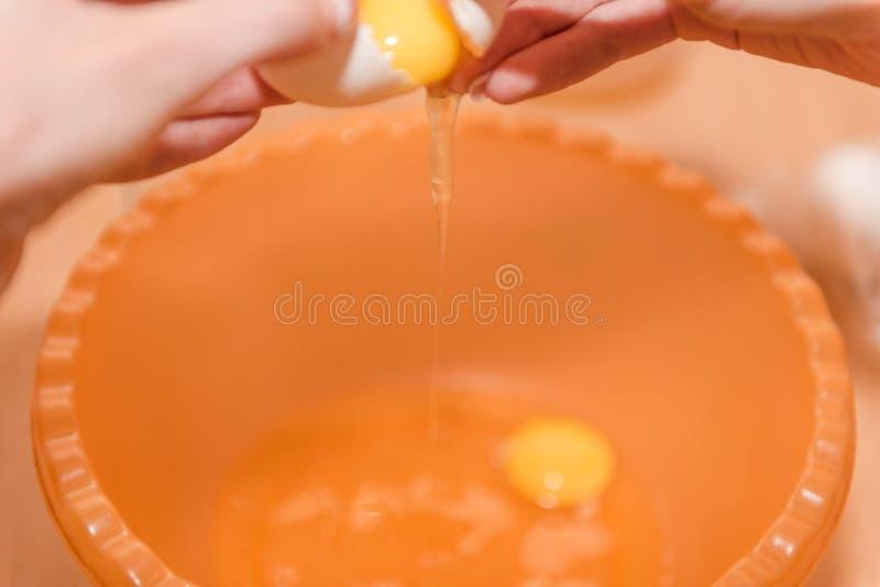 A menina quebra o ovo Cozinhando o alimento caseiro Ovos para o teste que cozinha a massa Alimento natural Cozimento home foto de stock
