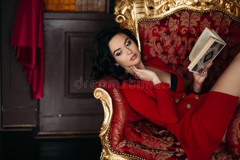 Menina quente no livro vermelho curto da terra arrendada do vestido, encontrando-se na biblioteca imagens de stock royalty free