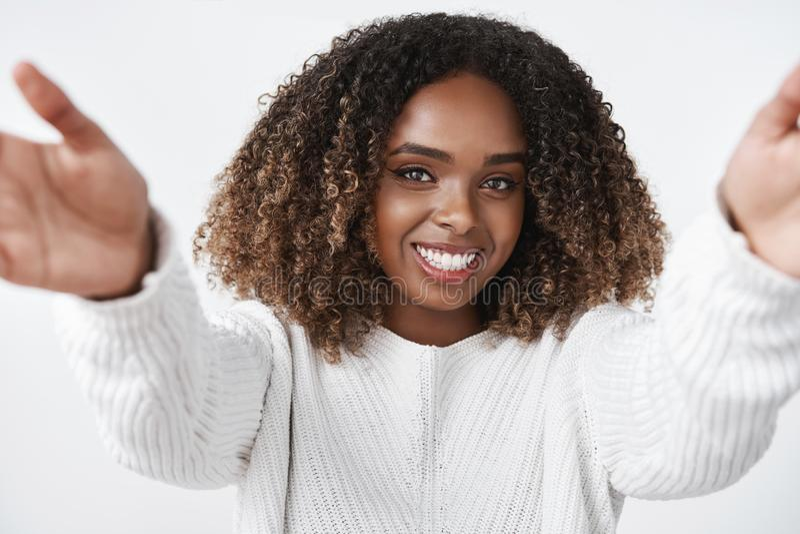 A menina quer aquecer abraços Fêmea afro-americano macia e bonito nas mãos de alargamento da camiseta para a câmera a afagar e fotografia de stock