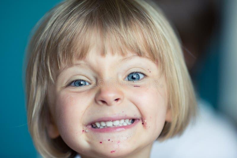 Menina real loura caucasiano de sorriso feliz dos povos do bebê novo com o retrato sujo do fim da boca em casa imagem de stock royalty free
