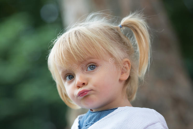 Menina real loura caucasiano dos povos do pensamento sério ou do bebê novo triste com o retrato do fim do rabo de cavalo exterior foto de stock royalty free
