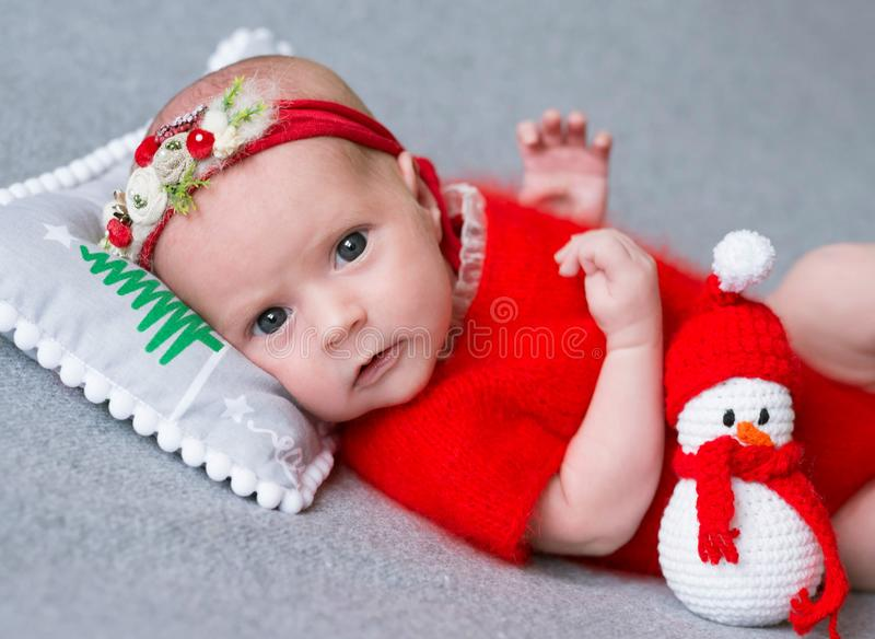 A menina recém-nascida em um terno do Natal está dormindo em um descanso do ` s do ano novo fotografia de stock